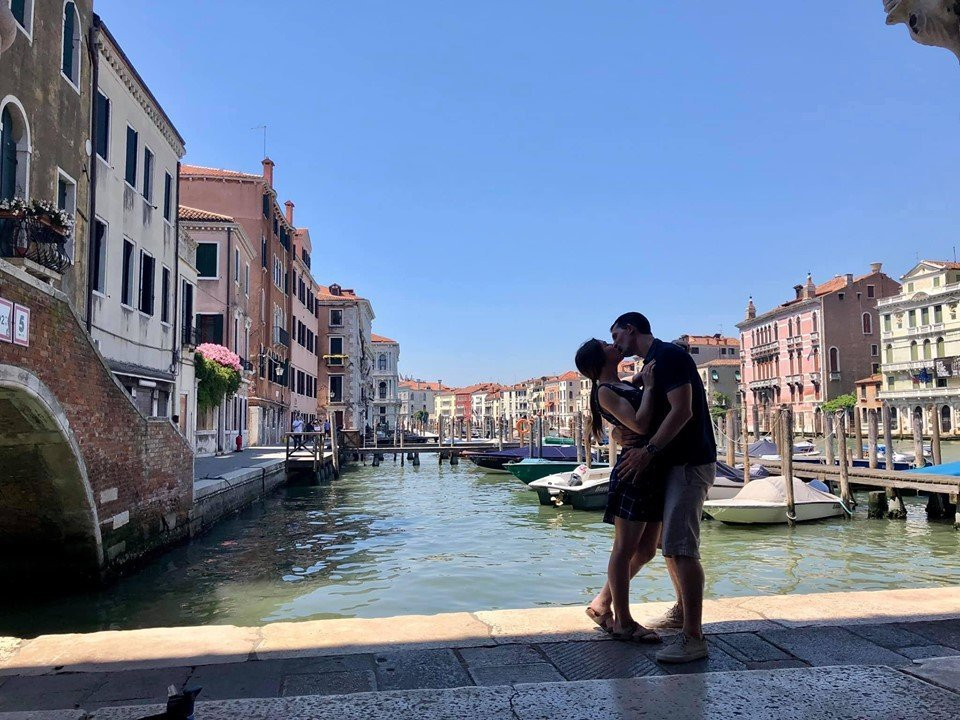 man and woman kissing by canal in venice