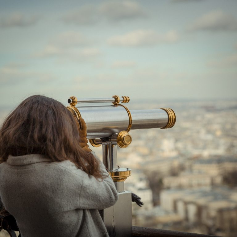person looking though telescope at city