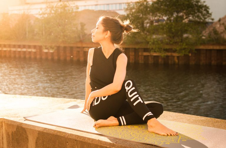 Woman wearing black stretching by water