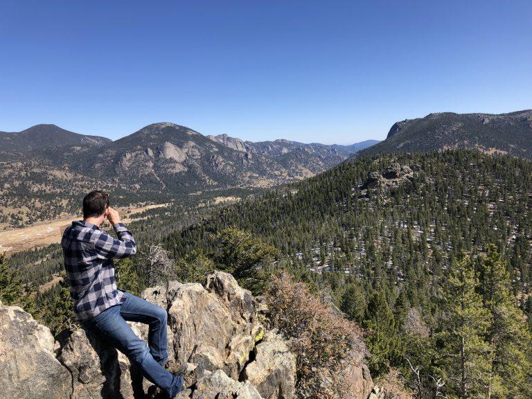 man looking at mountains sitting on rock