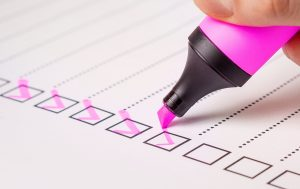 pink highlighter making checkmark on paper
