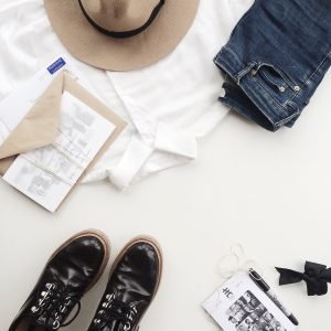 White Dress Shirt Near Blue Jeans and Envelope on Table