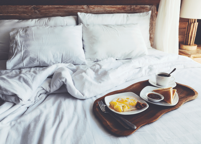 breakfast on tray on white bed