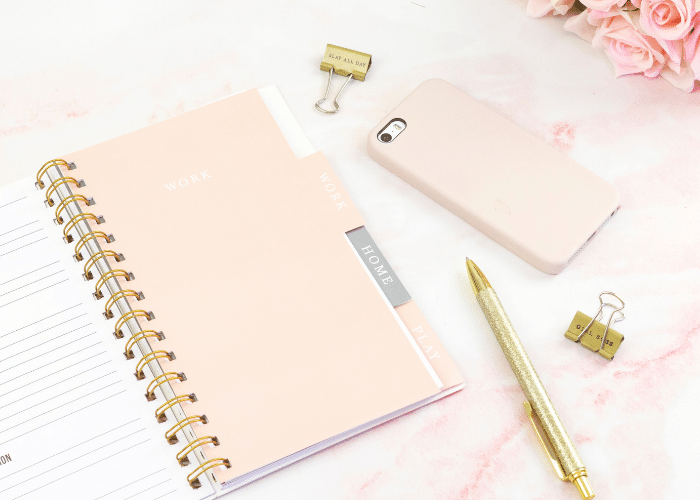 pink planner with phone pen binder clips and flowers
