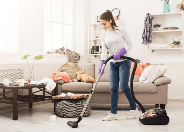 woman vacuuming carpet in house