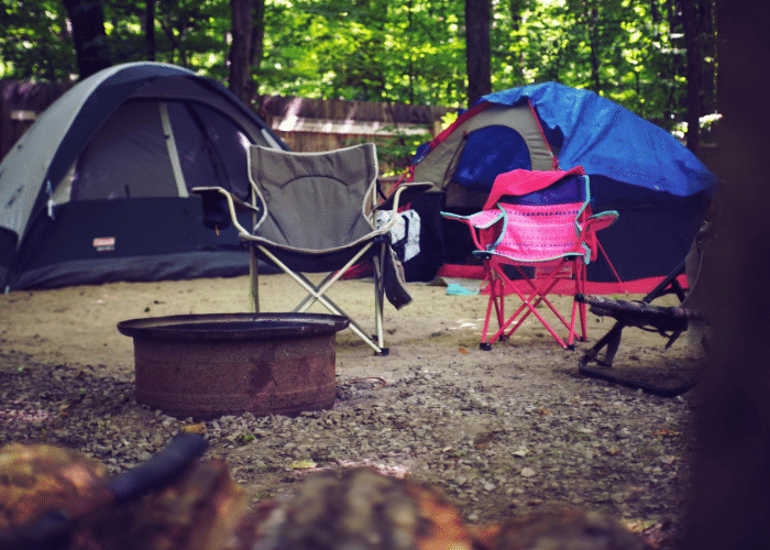 tents and camp chairs next to fire pit ring