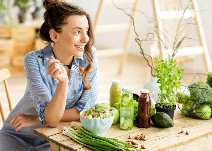 woman eating vegetables on table with plants
