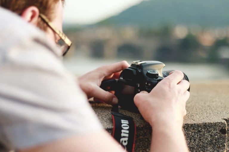 Man in White Top Holding Black Canon Dslr Camera on Gray Concrete Ledge