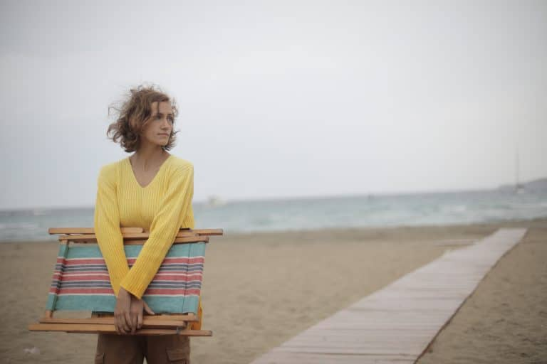 Photo of Woman in Yellow Long Sleeve Shirt Standing at the Beach Carrying Wooden Folding Beach Chair