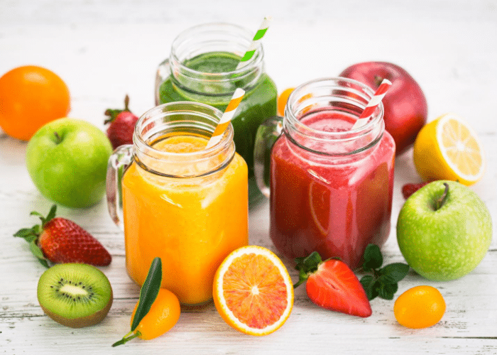 fruit smoothies in glass jars with fruit around them