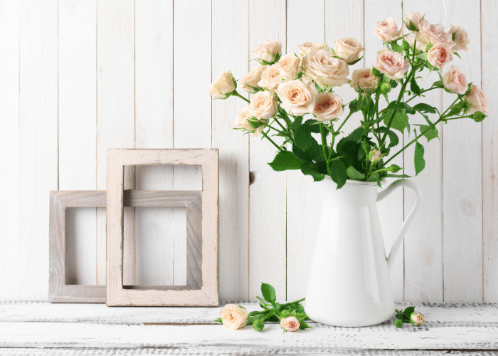 vase with pink flowers next to wood frames