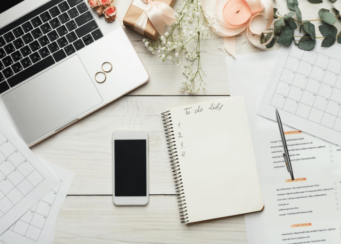 to do list on notebook next to laptop phone and papers