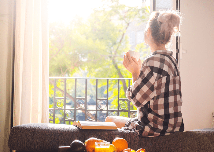 woman sitting by window with mug and book