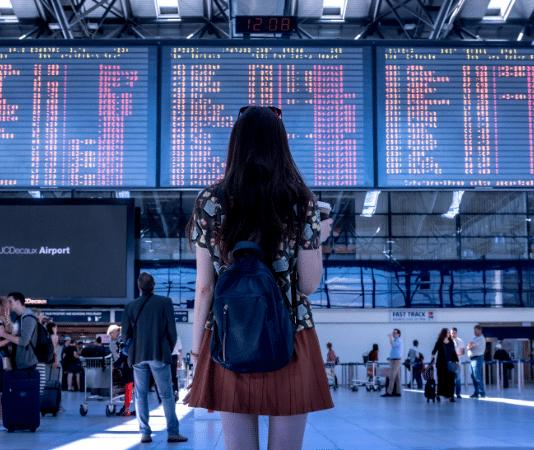 woman at airport looking at board