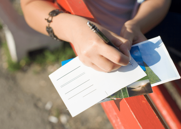 person writing postcard