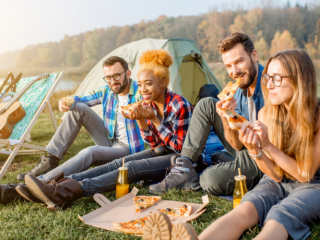 people eating pizza while camping